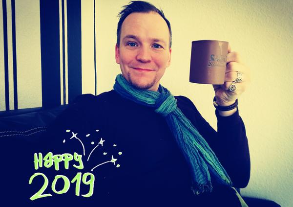 Jan mit einer Kaffeetasse, die er zum Gruß für das Jahr 2019 erhebt