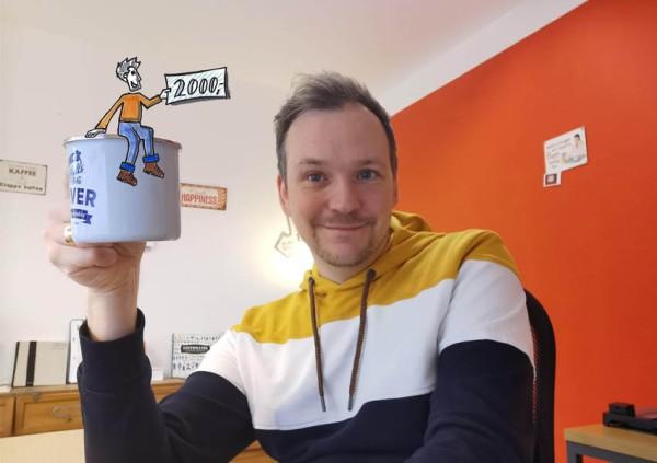 Jan erhebt die Kaffeetasse und stößt auf 2000 gesammelte Spenden für ein Indoor Klettergerüst für den Marien-Kindergarten an